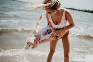Mom enjoying herself at the beach with her child. Intended to illustrate the confidence that comes with Mommy Makeover procedure.
